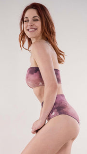Left side view of model wearing the reversible Peacock high waist bikini bottom in the Rose Quartz side in the colors pink and purple