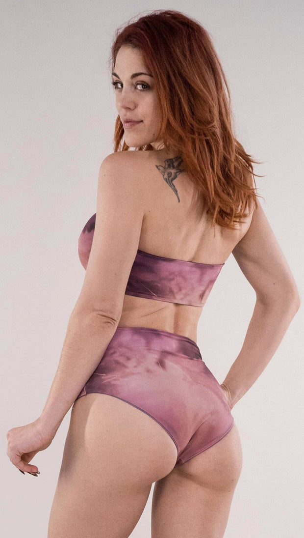 Back side view of model wearing the reversible Peacock bandeau in the Rose Quartz side in the colors pink and purple