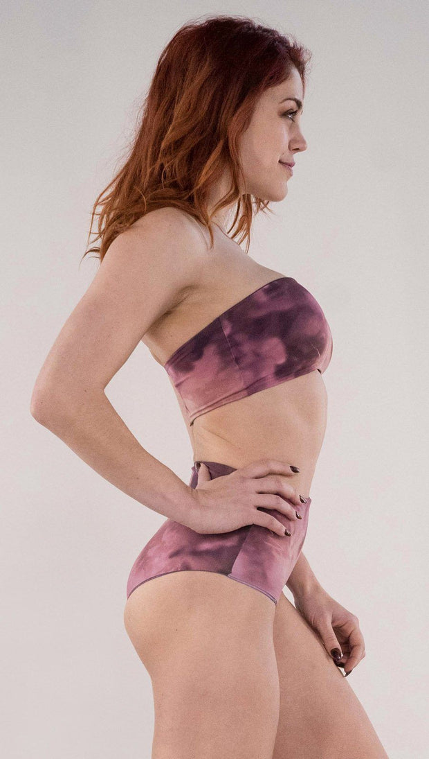 Right side view of model wearing the reversible Peacock high waist bikini bottom in the Rose Quartz side in the colors pink and purple
