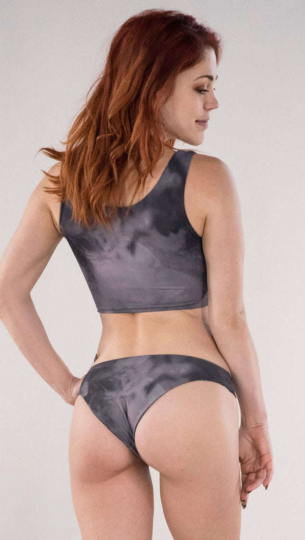 Back view of model wearing the reversible Celestial Mosaic low rise bikini bottom in the Smokey Quartz side in the colors gray and dark gray