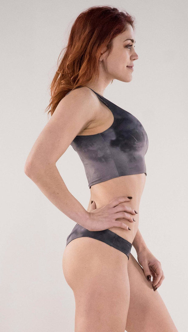 Right side view of model wearing the reversible Celestial Mosaic low rise bikini bottom in the Smokey Quartz side in the colors gray and dark gray
