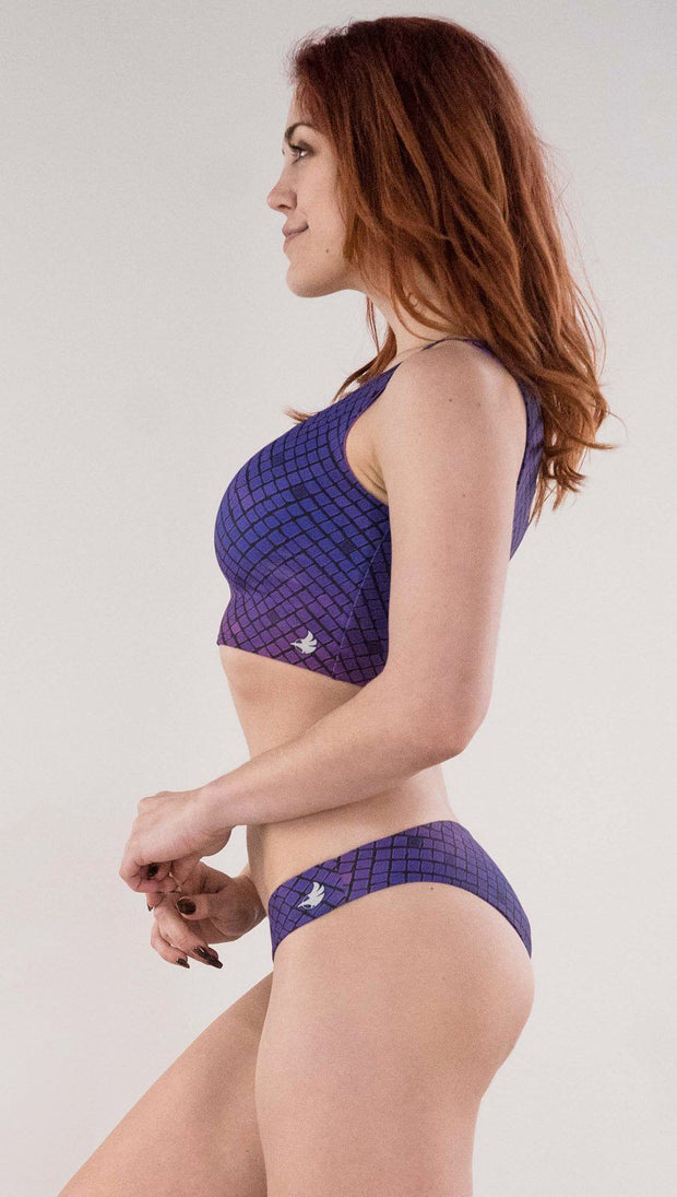 Left side view of model wearing the reversible Rainbow Mosaic low rise bikini bottom in the mosaic tile on this side in the color purple