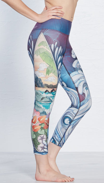 close up side view of island surf board and waves themed printed capri leggings