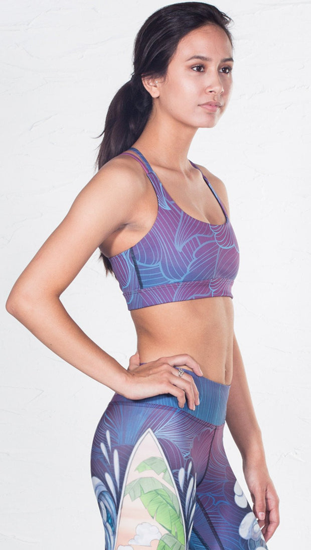 closeup right side view of model wearing surf and flower inspired printed sports bra