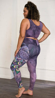 left side view of model wearing peacock themed full length leggings