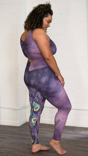 right side view of model wearing peacock themed full length leggings