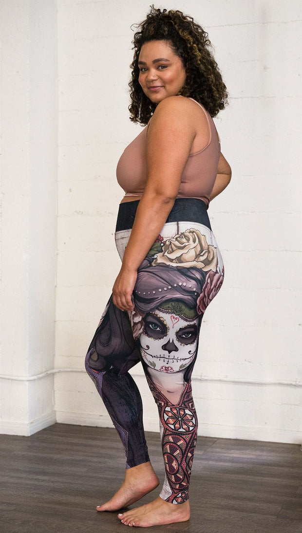 Right side view of model wearing mashup Sugar Skull and Dia De Los Muertos themed printed full length leggings