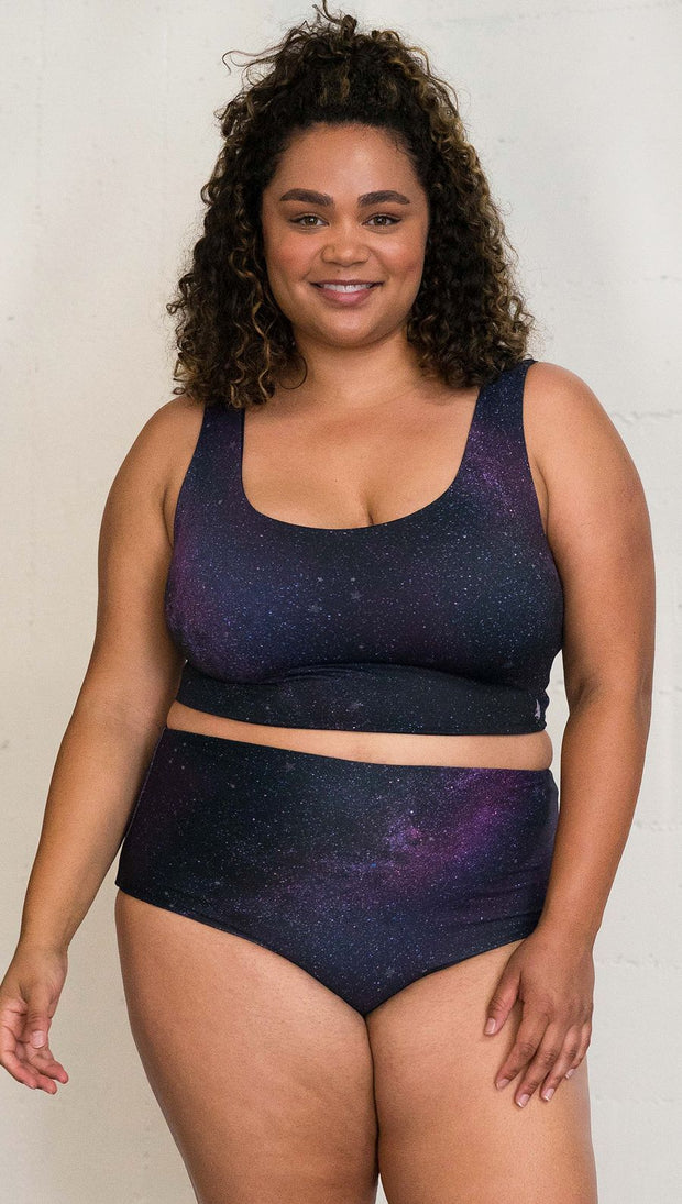 Closeup front view of model wearing reversible high-waist bikini bottom with celestial galaxy print on one side and black leather texture print on the opposite side