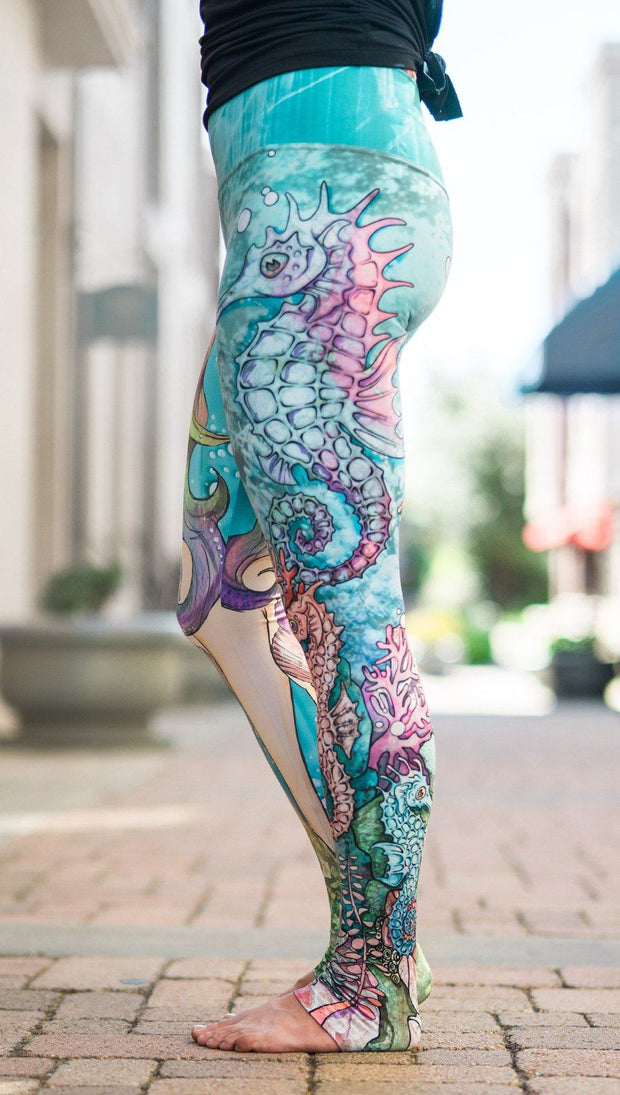 left side view of model wearing under the sea mermaid and seahorse mashup printed full length leggings