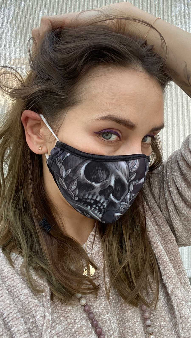 Right side view of model wearing a black mask with a large skull in grey