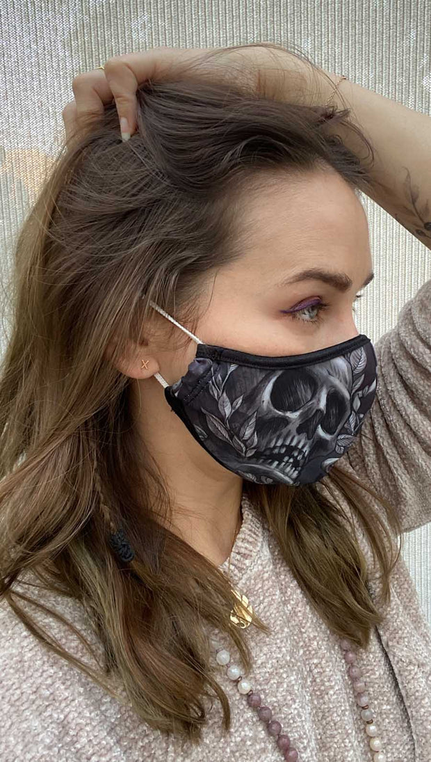 Right side view of model wearing a black mask with a grey skull