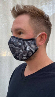 Left side view of male model wearing a black mask with grey branches