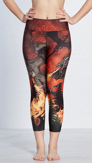 closeup front view of model wearing fire breathing dragon themed printed capri leggings