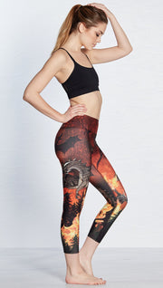 right side view of model wearing fire breathing dragon themed printed capri leggings