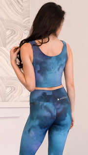 Back view of model wearing reversible tank top with ethereal dark blue water print on one side and textured watercolor print on the reverse side