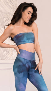 right side view of model wearing reversible bandeau top with ethereal dark blue water print on one side and textured watercolor print on the reverse side