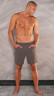 Front view of model wearing men's taupe performance shorts with slim fit.