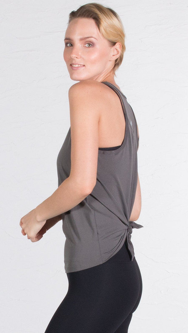 closeup left side view of model wearing gray tie back sports tank top