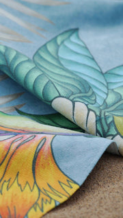 closeup view of design of beach towel with tropical floral design and blue background
