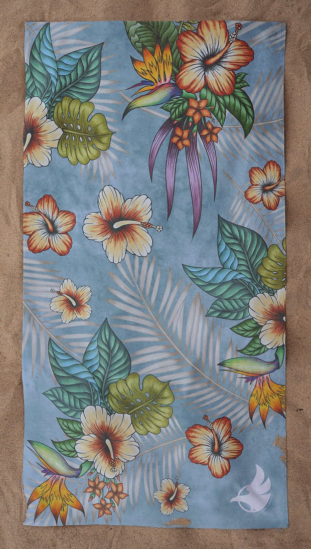 top view of beach towel with tropical floral design and blue background
