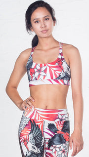 closeup front view of model wearing red and black bird / flower inspired printed sports bra
