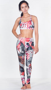 front view of model wearing red and black bird / flower inspired printed sports bra