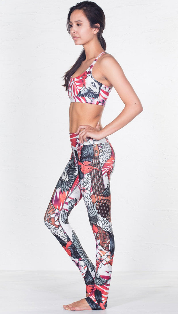 left side view of model wearing red and black bird / flower inspired printed sports bra