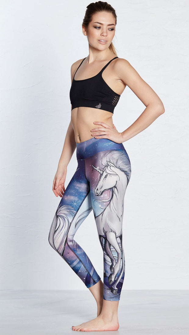 left side view of model wearing unicorn design printed capri leggings