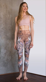 front view of model wearing full length leggings with printed jackalope design