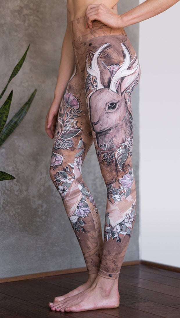 closeup left side view of model wearing full length leggings with printed jackalope design