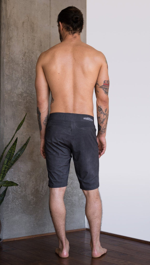 back view of model wearing charcoal black printed mens performance shorts