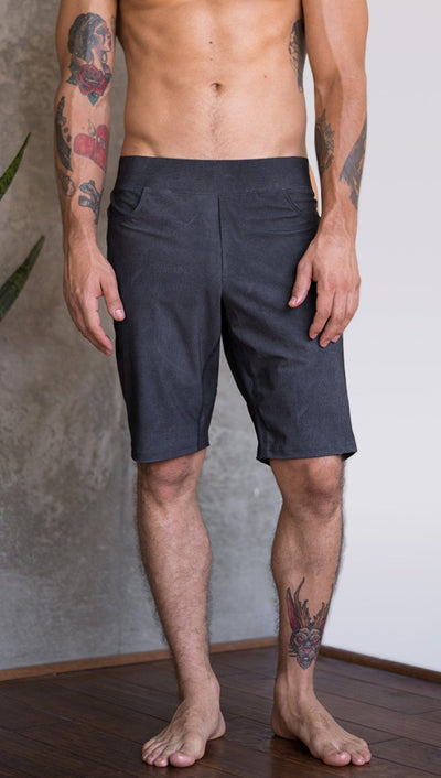 closeup front view of model wearing charcoal black printed mens performance shorts