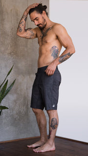 left side view of model wearing charcoal black printed mens performance shorts