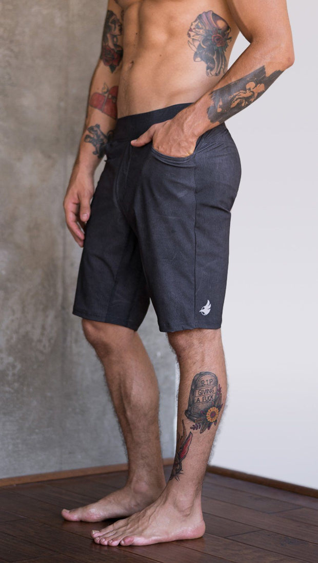 closeup left side view of model wearing charcoal black printed mens performance shorts