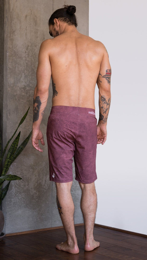 back view of model wearing brick red printed mens performance shorts