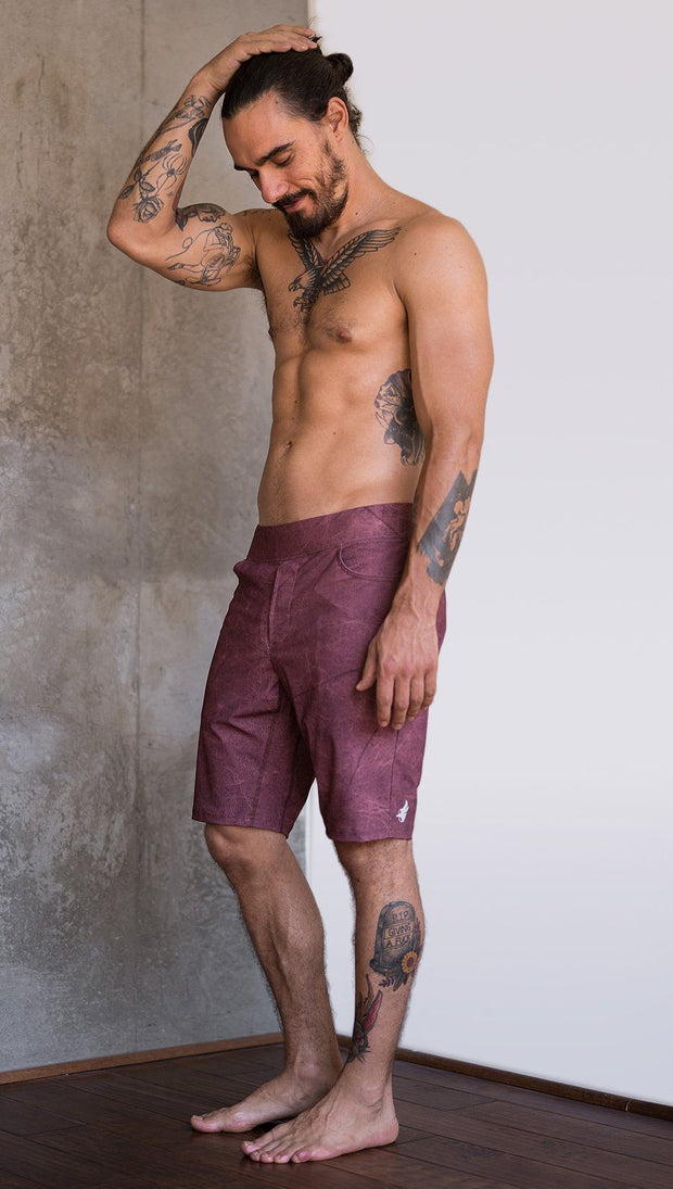 left side view of model wearing brick red printed mens performance shorts