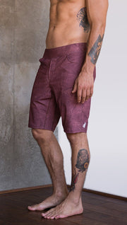 closeup left side view of model wearing brick red printed mens performance shorts