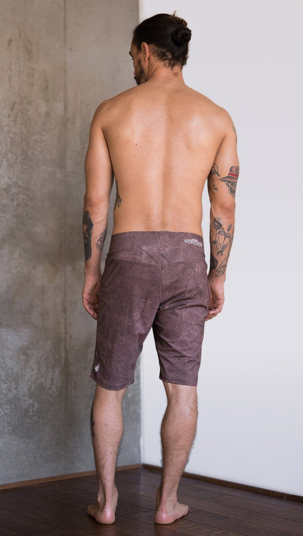 back view of model wearing cannabis inspired printed mens performance shorts