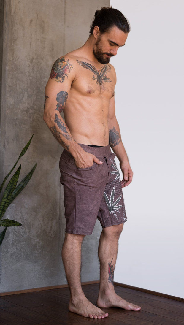 right side view of model wearing cannabis inspired printed mens performance shorts