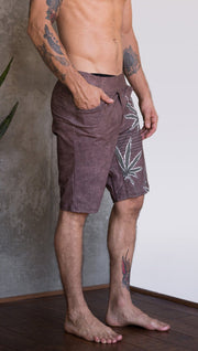 closeup right side view of model wearing cannabis inspired printed mens performance shorts