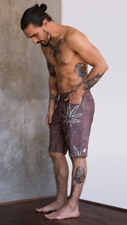 left side view of model wearing cannabis inspired printed mens performance shorts