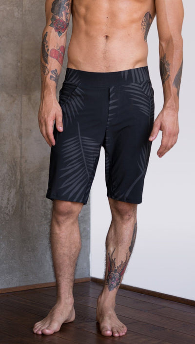 front view of model wearing tropical palm fronds printed mens performance shorts