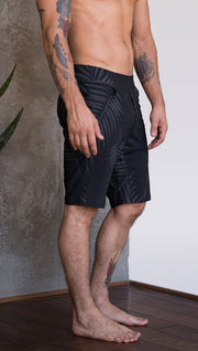 right side view of model wearing tropical palm fronds printed mens performance shorts
