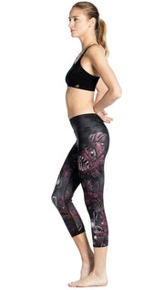left side view of model wearing deep sea angler fish printed capri leggings and black sports top