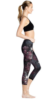 right side view of model wearing deep sea angler fish printed capri leggings and black sports top
