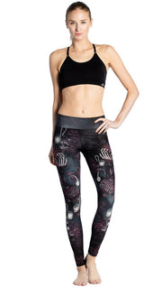 front view of model wearing deep sea angler fish printed full length leggings and black sports top