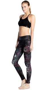 model standing slightly sideways wearing deep sea angler fish printed full length leggings and black sports top