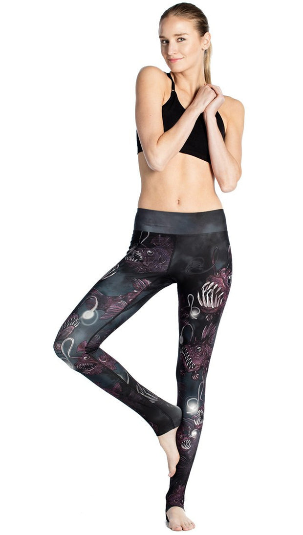 front view of model posing wearing deep sea angler fish printed full length leggings and black sports top
