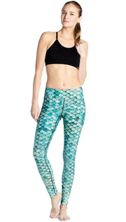 front view of model wearing teal mermaid / fish scale printed full length leggings