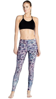 front view of model wearing purple mermaid scale themed printed full length leggings
